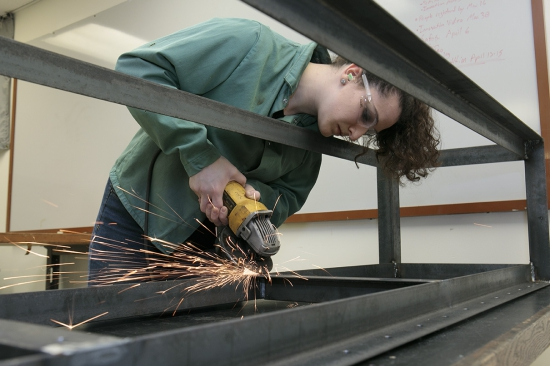 Mechanical engineering major Bella Balzano sands the frame of the stage-automation system.